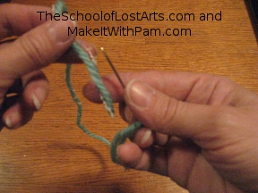 Hold needle point up and thread end down